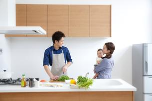 キッチンで料理する若い男性との赤ちゃんを抱く若い女性の写真素材 [FYI01467112]