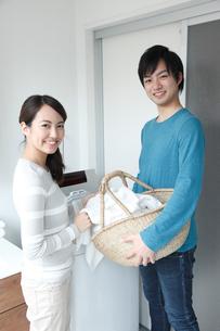 洗濯機の前で微笑む若いカップルの写真素材 [FYI01467141]