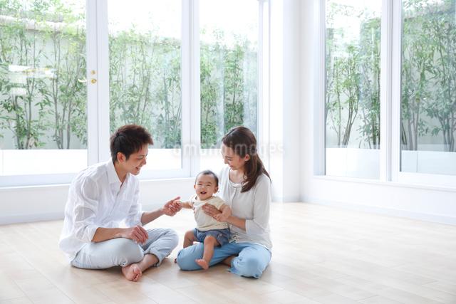 床で赤ちゃんをあやす若いカップルの写真素材 [FYI01467142]