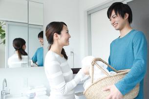 洗濯機の前で微笑みあう若いカップルの写真素材 [FYI01467214]