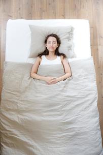 ベッドで睡眠中の若い女性の写真素材 [FYI01467249]
