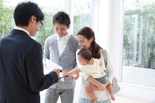 モデルハウスで説明を受ける赤ちゃん連れの若い3人家族の写真素材 [FYI01467271]