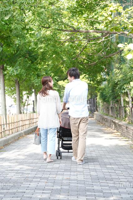 ベビーカーを押し散歩する後姿の若いカップルの写真素材 [FYI01467277]