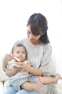 離乳食を赤ちゃんに与える若い母親の写真素材 [FYI01467291]