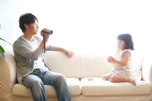 ソファで娘を撮影する父親の写真素材 [FYI01467305]