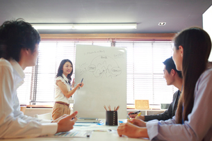 シェアオフィスでミーティングをする私服の男女ビジネスマン4人の写真素材 [FYI01467311]