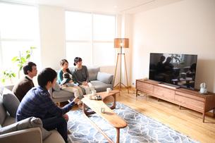 リビングでテレビを観る3世代ファミリーの写真素材 [FYI01467317]