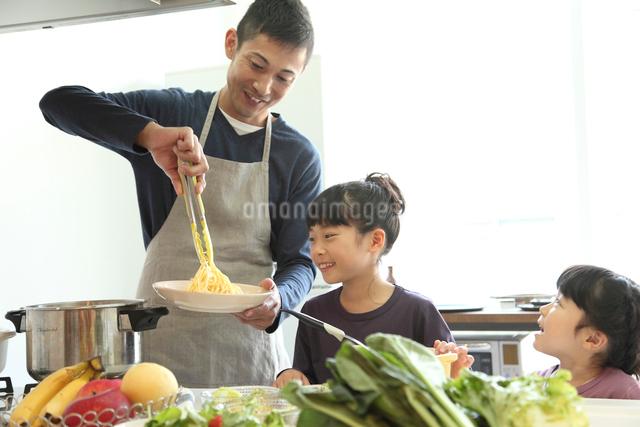 料理をする父親と幼い女の子きょうだいの写真素材 [FYI01467373]