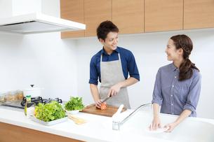 キッチンで微笑む若いカップルの写真素材 [FYI01467375]