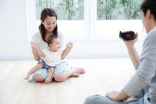 動画を撮る若い3人家族の写真素材 [FYI01467391]