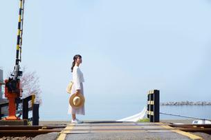 踏切で立ち止まって景色を見渡す女性の写真素材 [FYI01467451]