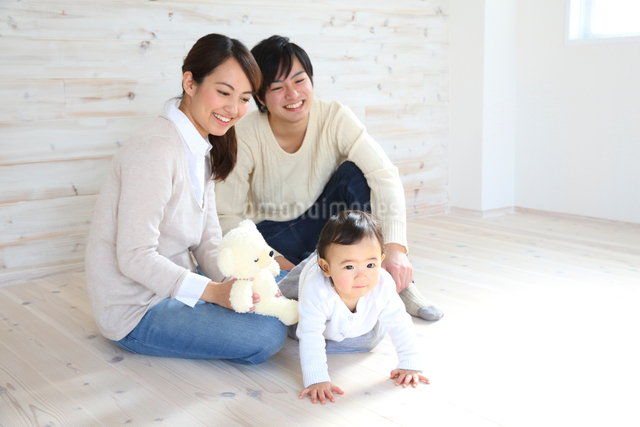 床でくつろぐ若い3人家族の写真素材 [FYI01467540]