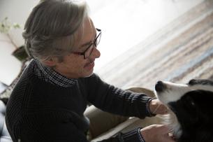 ソファで愛犬と過ごすシニア男性の写真素材 [FYI01467550]