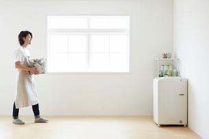 シンプルな部屋で洗濯物を洗濯機に運ぶ男性の写真素材 [FYI01467618]