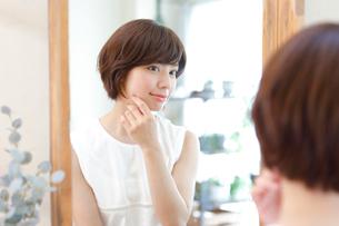鏡の前でスキンケアをする女性の写真素材 [FYI01467681]