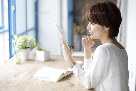 窓辺でタブレット端末を持つ若い女性の写真素材 [FYI01467747]