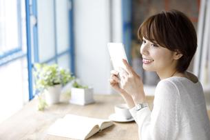 窓辺でタブレット端末を持つ若い女性の写真素材 [FYI01467806]