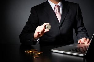 パソコンでビットコインのビジネスをするスーツを着た男性の写真素材 [FYI01467820]