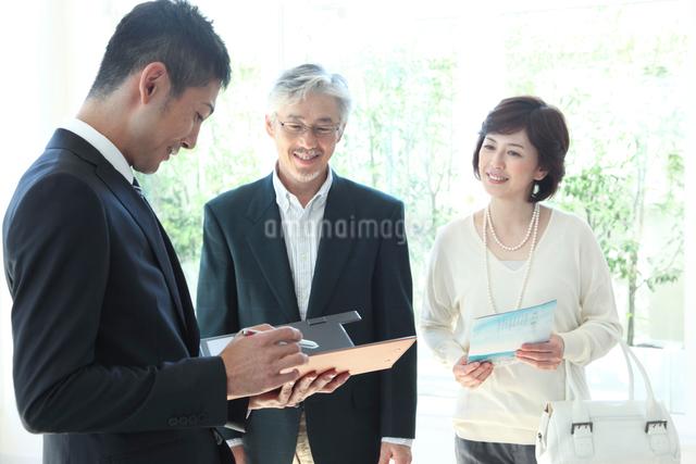 部屋の見学に来たミドルカップルを接客するビジネスマンの写真素材 [FYI01467850]