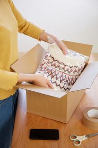 畳んだセーターを箱に詰める女性の手元の写真素材 [FYI01467867]