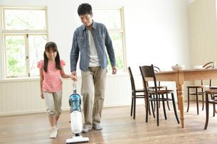 掃除機をあてる父親を手伝う女の子の写真素材 [FYI01467950]