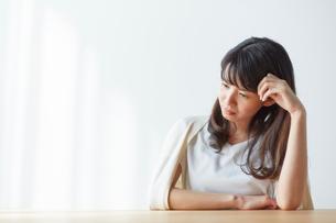 テーブルで肘をついて下を向く女性の写真素材 [FYI01467971]
