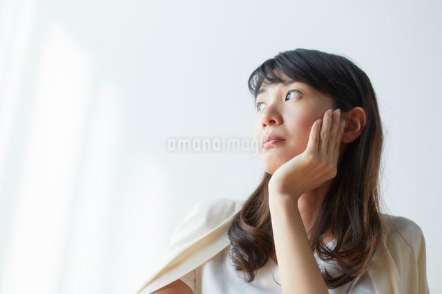 頬杖を付いて窓の外を見る女性の写真素材 [FYI01467976]