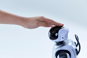 ロボットの頭を撫でる人間の手の写真素材 [FYI01467980]