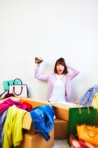 箱から出る服や鞄などが散らかった部屋と財布を持つ女性の写真素材 [FYI01467994]