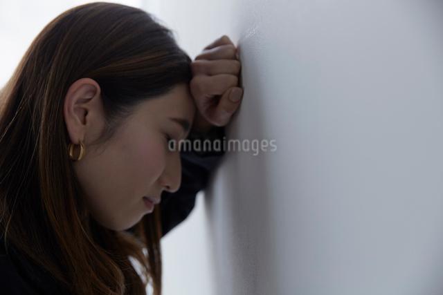 壁に向かって落ち込む女性の写真素材 [FYI01468012]