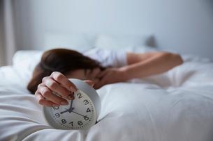 ベットの上で目覚まし時計を握ってあくびをする女性の写真素材 [FYI01468034]