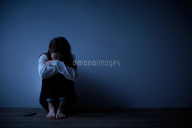 暗い部屋の中で小さくなる女性の写真素材 [FYI01468069]