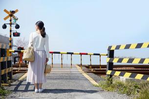 踏切で電車待ちをする女性の写真素材 [FYI01468107]