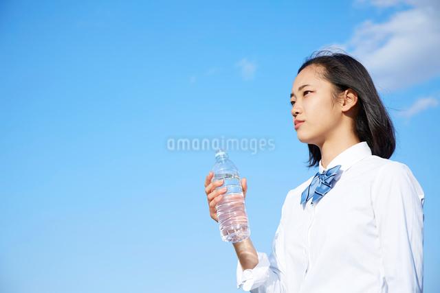 青空の下でペットボトルの水を飲む女子高生の写真素材 [FYI01468168]