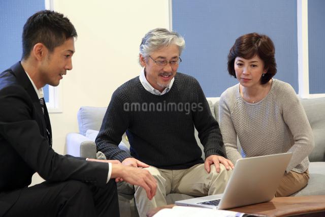自宅でビジネスマンの説明を受けるミドルカップルの写真素材 [FYI01468243]