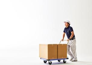 白バックの空間で荷物の乗った台車を運ぶ作業着の男性の写真素材 [FYI01468305]