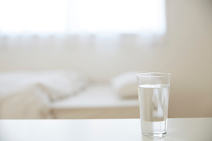 ベッド横のテーブルに置かれたグラスの水の写真素材 [FYI01468324]