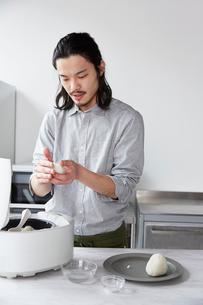 キッチンでおにぎりを握る男性の写真素材 [FYI01468355]