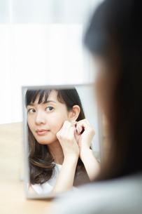 鏡を見て身支度をする女性の写真素材 [FYI01468359]