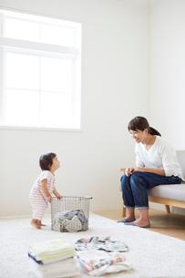 洗濯カゴを持って母と目を合わせる赤ちゃんの写真素材 [FYI01468404]