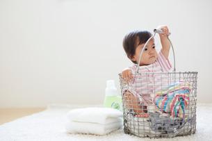 洗濯カゴの中に洗濯物と一緒に入っている赤ちゃんの写真素材 [FYI01468411]