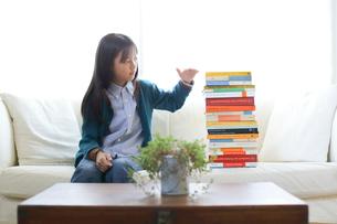 山積みの本を計るソファの少女の写真素材 [FYI01468520]