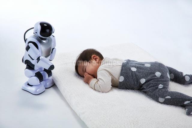 お昼寝する赤ちゃんを見守るロボットの写真素材 [FYI01468521]