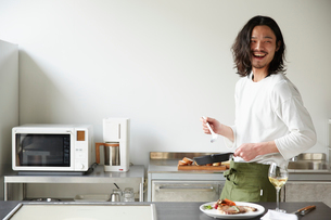 キッチンで料理をする男性の写真素材 [FYI01468527]