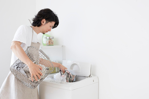 洗濯物を洗濯機に入れる男性の写真素材 [FYI01468555]