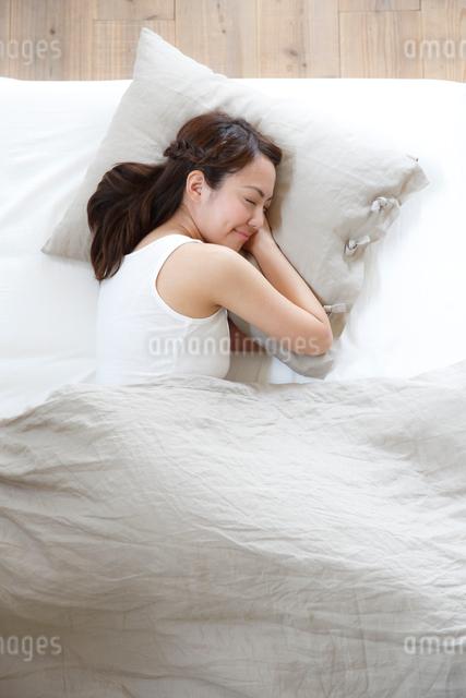 ベッドで睡眠中の若い女性の写真素材 [FYI01468570]