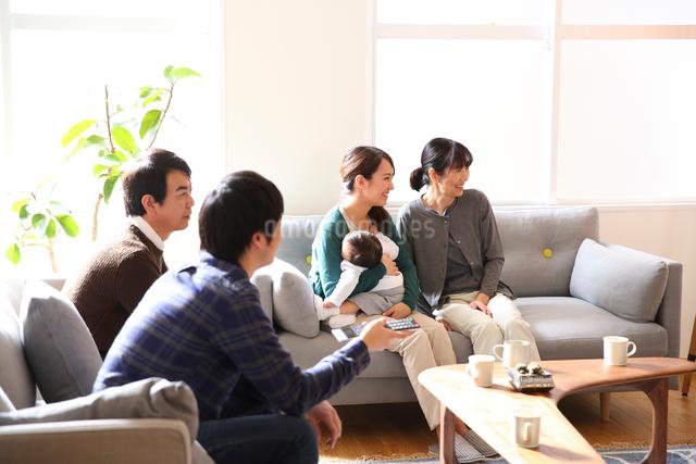 リビングでテレビを観る3世代ファミリーの写真素材 [FYI01468573]