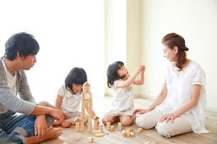 床で積木で遊ぶ4人家族の写真素材 [FYI01468591]
