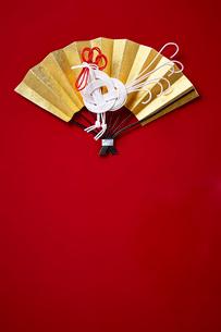 赤い背景の上の金の扇子と酉型の水引の写真素材 [FYI01468658]