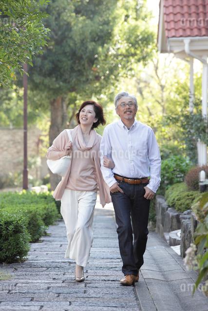 住宅街を散歩するミドルカップルの写真素材 [FYI01468666]